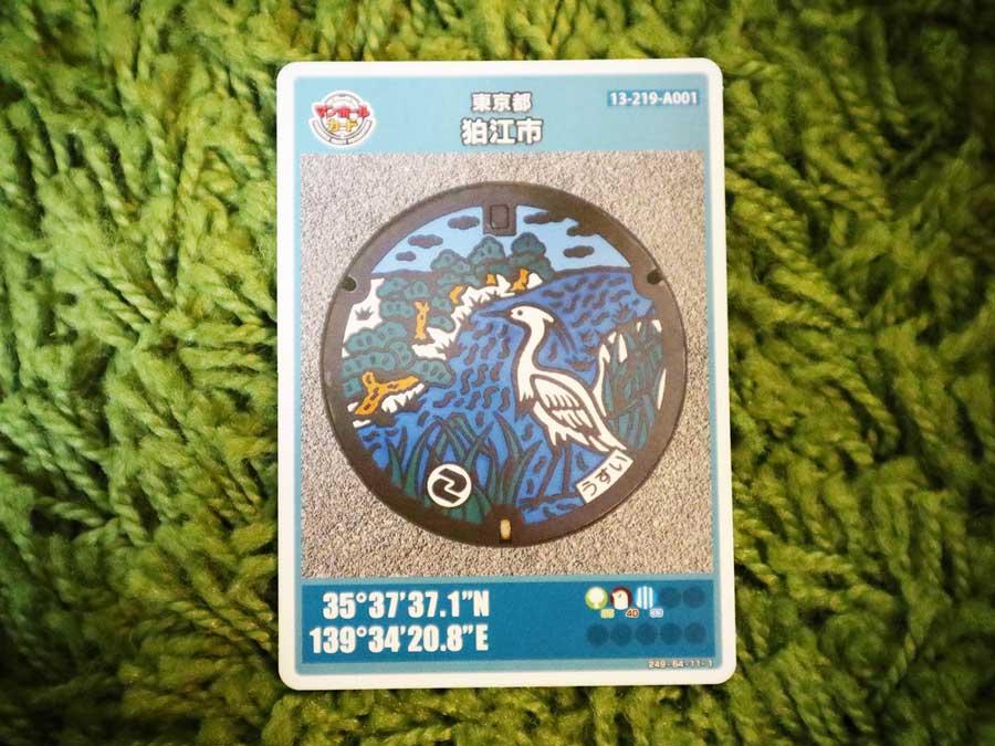 狛江市のマンホールカード。表は多摩川五本松とコサギ、多摩川のデザインのマンホールが掲載されている